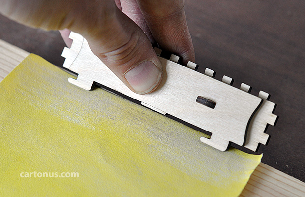Chamfer to corners of latch hooks using sandpaper. For soft-closing lid.